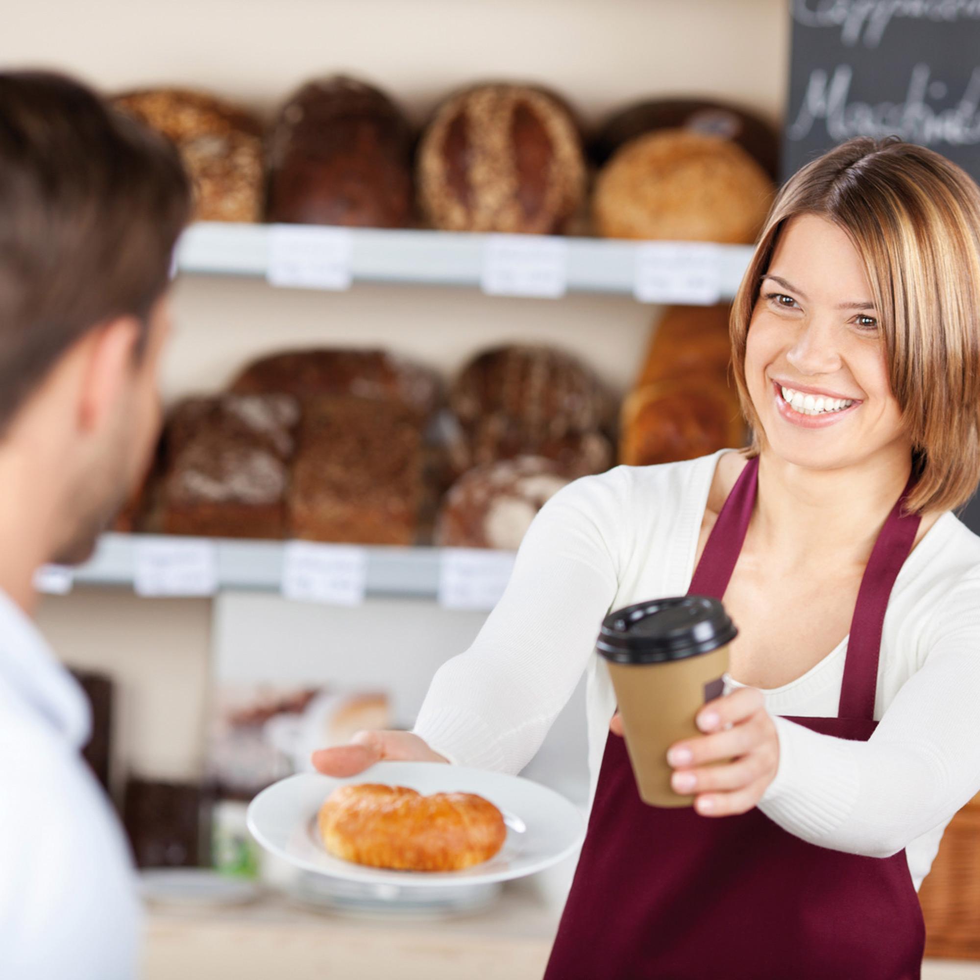 Verkäuferin eines geplanten Café in der studiosus 5 Wohnanlage reicht Kunden Croissant und Kaffee